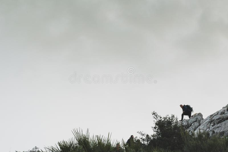 Person on Rocky Mountain Under White Cloudy Sky stock image