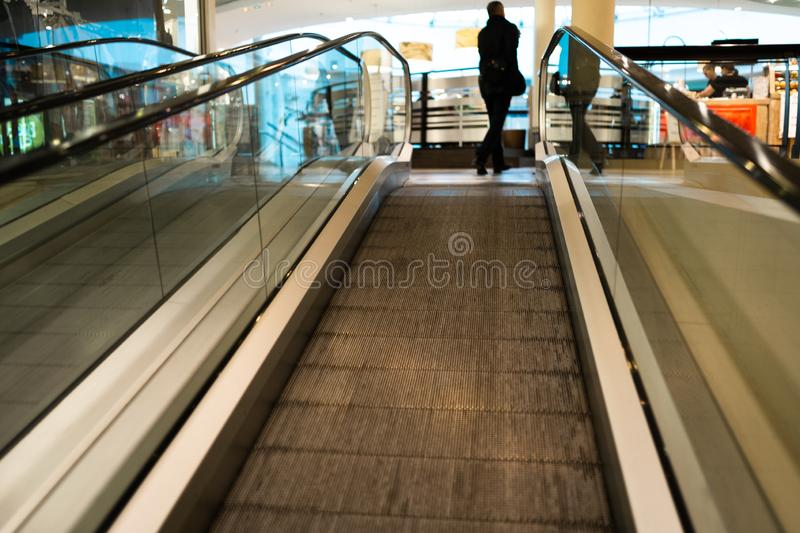 Person rush on escalator motion blurred in the background. Shopping centre royalty free stock photos