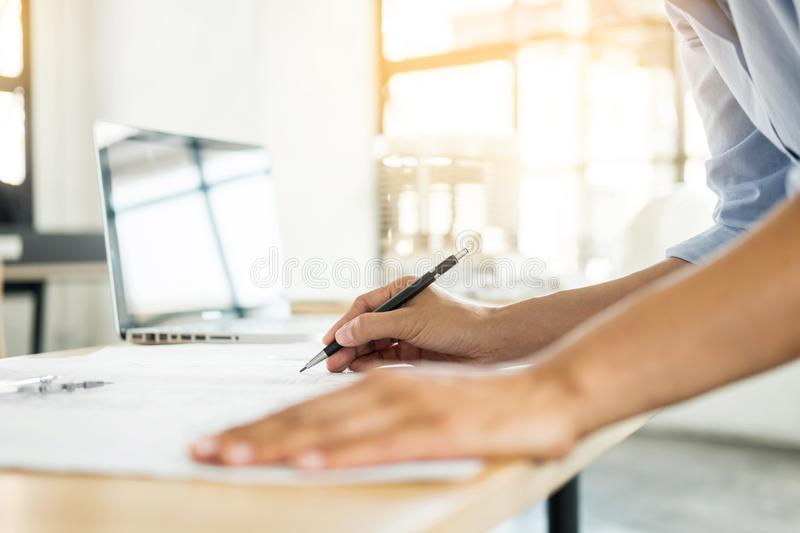 Person`s engineer Hand Drawing Plan On Blue Print with architect. Equipment, Architects working at the table stock photography