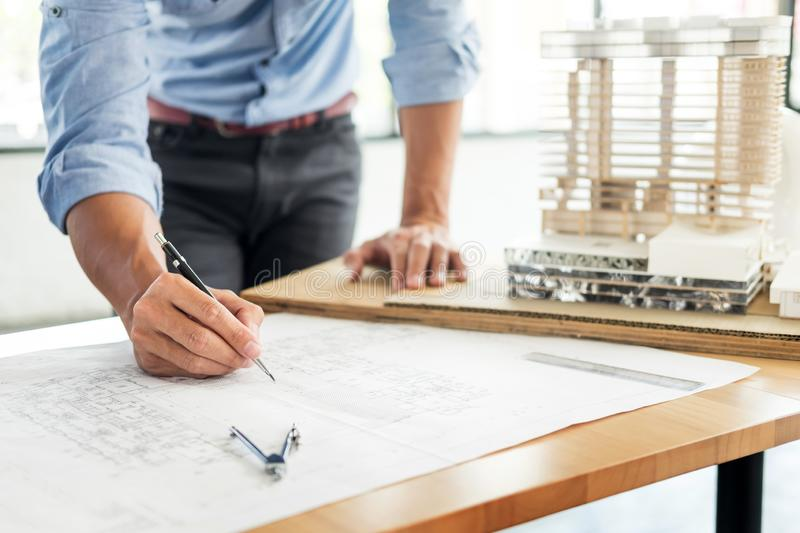 Person`s engineer Hand Drawing Plan On Blue Print with architect. Equipment, Architects working at the table royalty free stock photo
