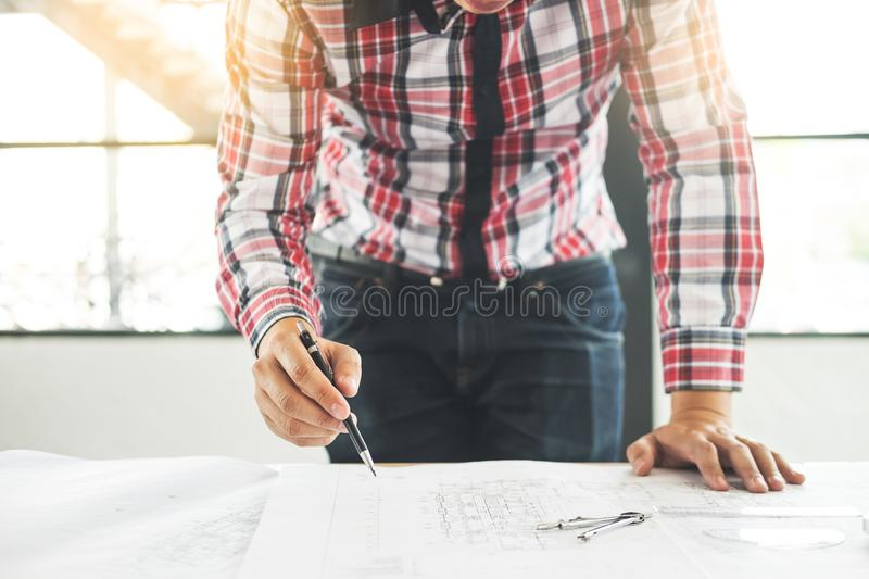 Person`s engineer Hand Drawing Plan On Blue Print with architect. Equipment, Architects working at the table royalty free stock images