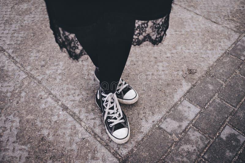 Person 's Füße tragen schwarz-weiße High-Top-Sneakers stockfoto