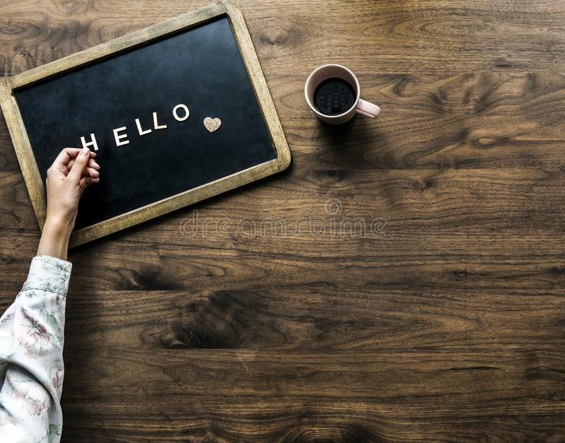 Person's Hand on Black Board With Hello Text Beside Brown Mug royalty free stock photography