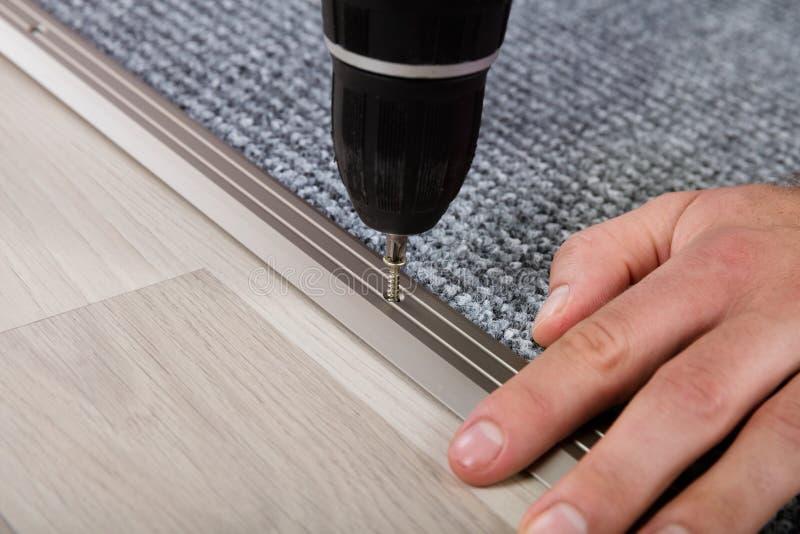 Person ` s Hand, die Teppich auf Boden installiert lizenzfreies stockbild