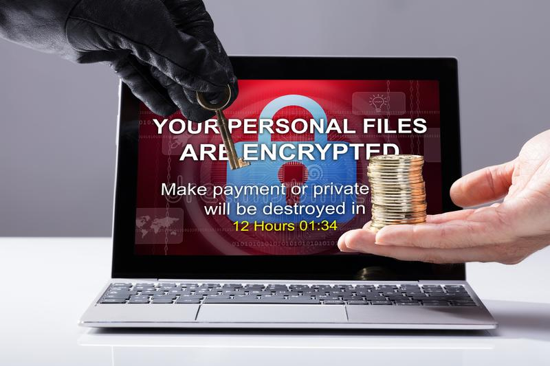 Person`s Hand Giving Stacked Coins To Hacker. Person`s Hand Giving Coins To Hacker In Exchange Of Security Key In Front Of Laptop royalty free stock image