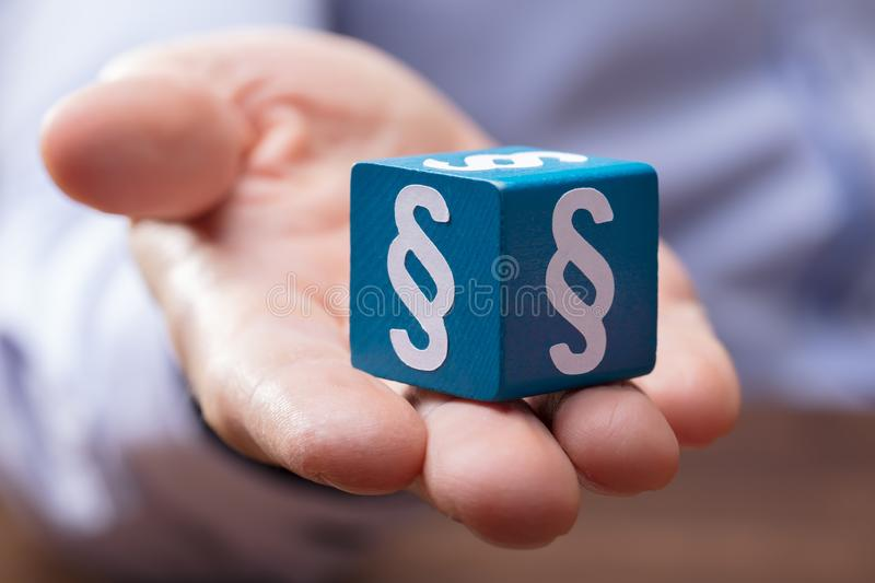 Person`s Hand Holding Paragraph Block. Close-up Of A Person`s Hand Holding Wooden Blue Block With Paragraph Symbols On It stock photography