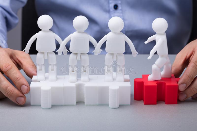Person`s Hand Joining Group Of Human Figures. A Person`s Hand Joining Group Of Human Figures Over Jigsaw Puzzle stock photography
