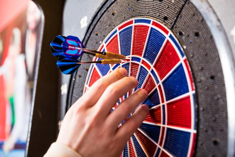 Person`s hand removing arrows from dartboard stock image