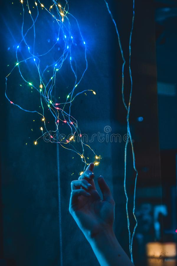 Person`s hand stretching and reaching out to colorful fantasy lights on a wire stock image