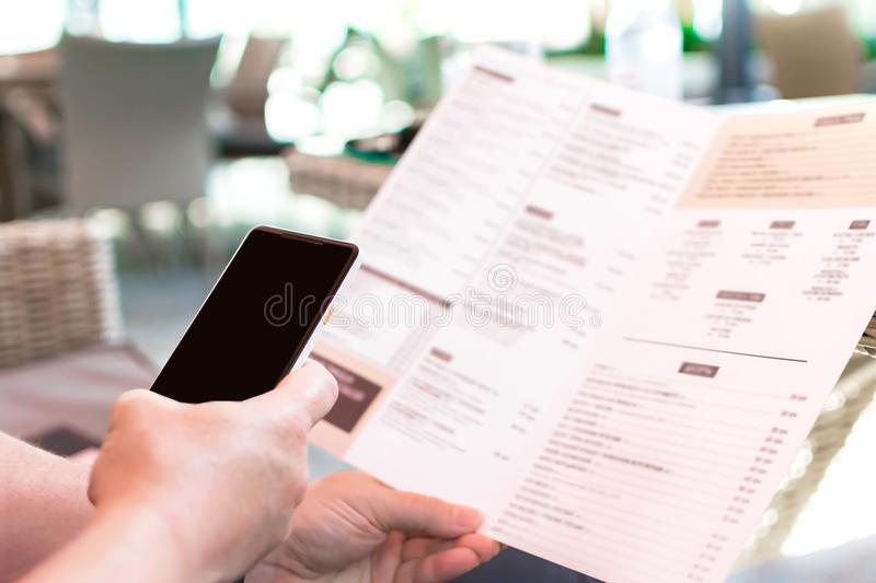 Person`s hands holding menu and mobile phone in a restaurant. A man in a cafe ordering food while sitting at table. Mockup for sm stock photos
