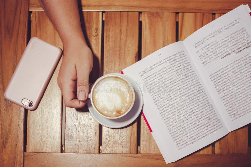 Person's houdt Witte Koffiemicrofoon met plaat op de bruine Woodenraad met wit en zwart boek stock afbeelding