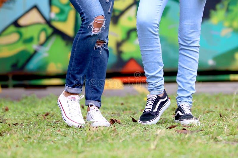 Person 's tragen weiße und schwarze Nieder-Top-Sneakers stockfotos
