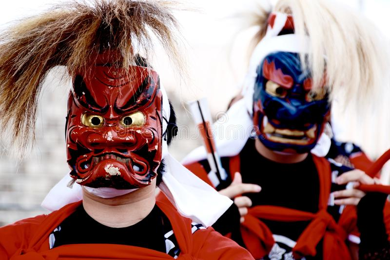 Person's Wearing Red and Blue Kabuki Masks stock image