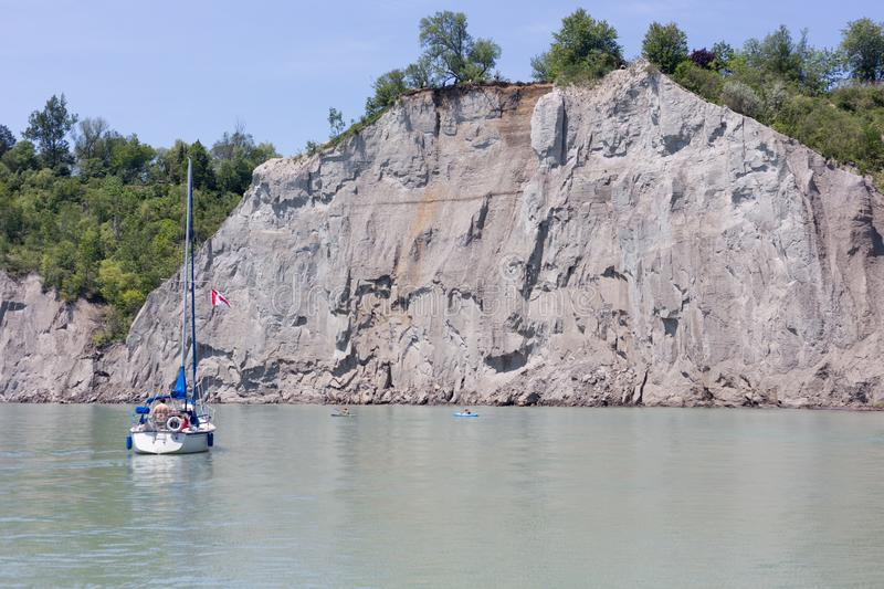Person sailing on sail boat people in kayaks in front of cliffs stock photography