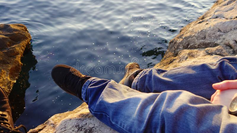 Person sat on rocks by the water in the evening sun. Low section of a person wearing black trainers, sat on a rock by the water in Croatia stock photography