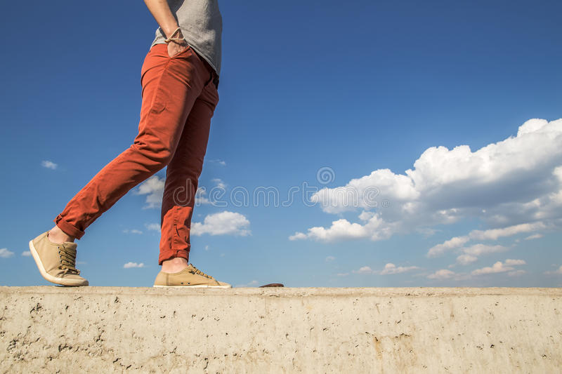 A person saunters on a concrete wall holding the her hands in their pockets. People comfortably saunters on a sunny warm day on a concrete wall holding the her royalty free stock images