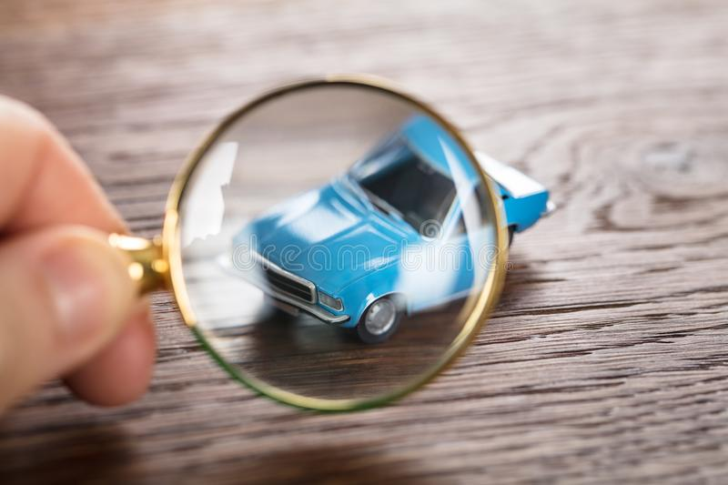Person Scrutinizing A Car Model. Using Magnifying Glass On Wooden Desk stock photos