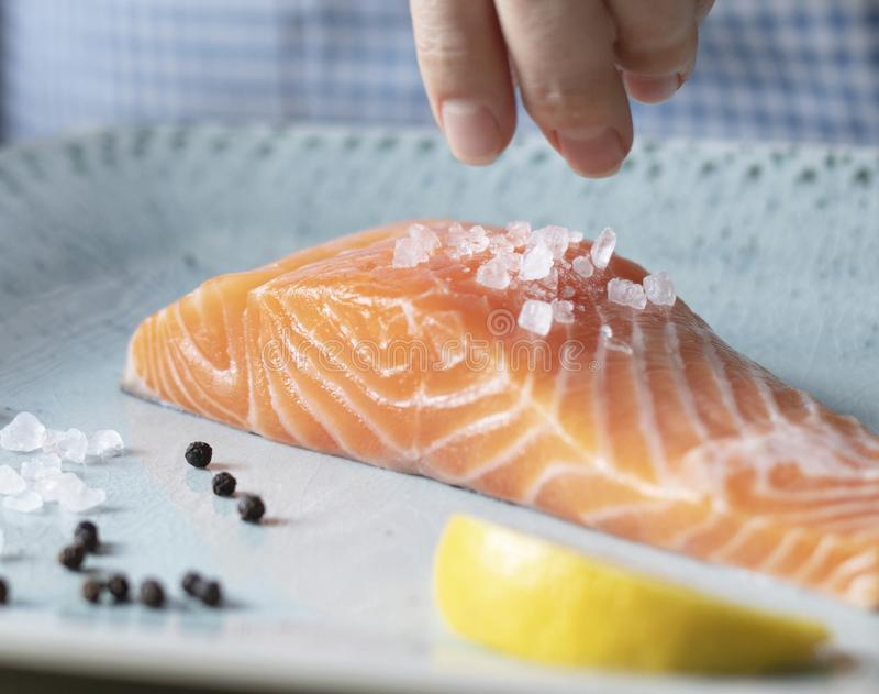 A person seasoning a fillet of salmon food photography recipe idea royalty free stock photography