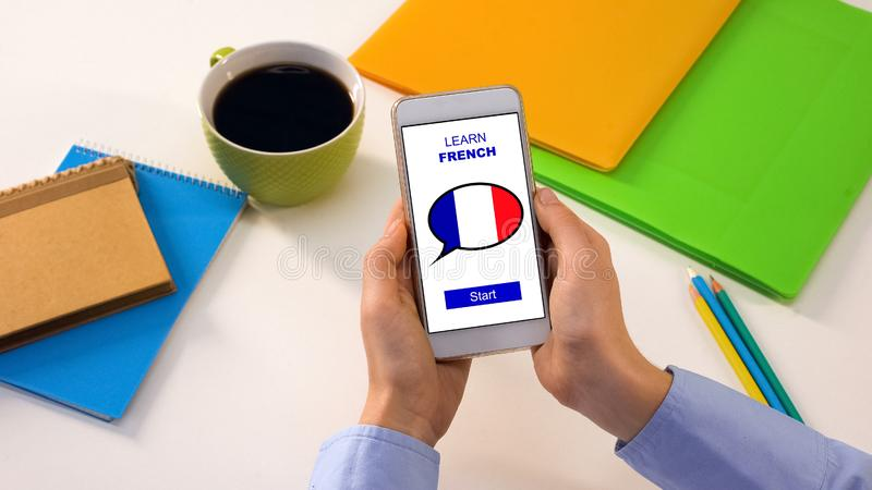 Person showing smartphone with learn French app, foreign language education. Stock photo stock image