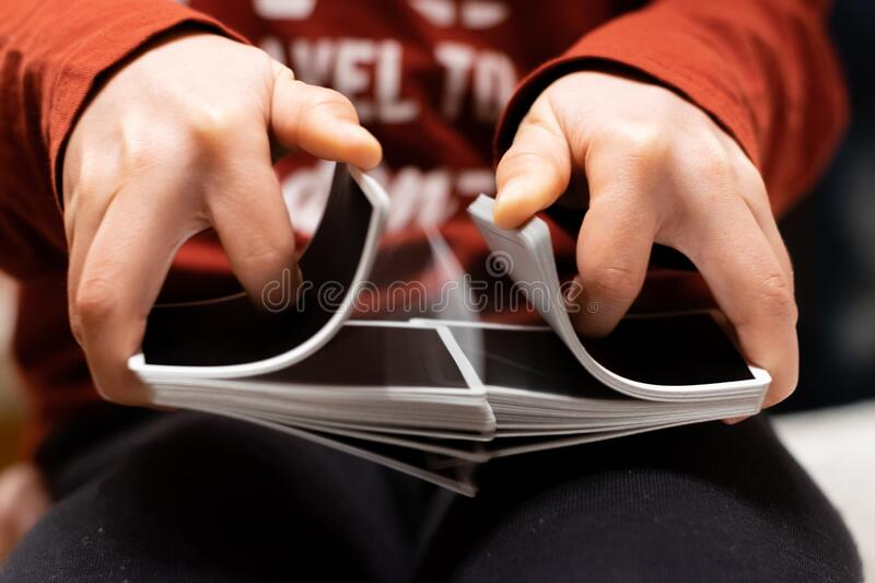 A person shuffling a deck of playing cards with a good color contrast between red and black colors.  royalty free stock photos