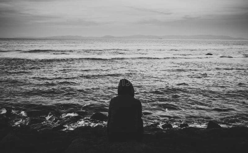 Person sitting alone by the beach. Sad mood, cold day in black and white royalty free stock image