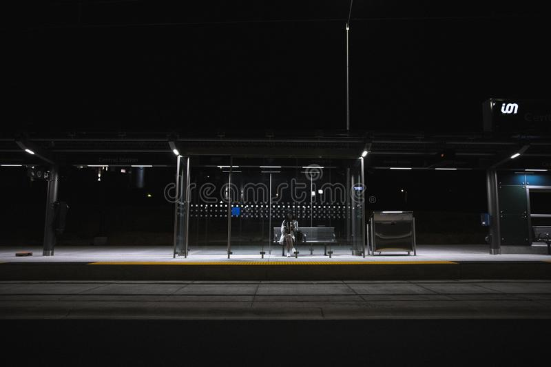 Person sitting alone at bus stop at night stock photo