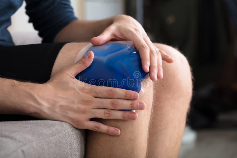 Person Sitting And Applying Ice-Gel-Satz auf Knie lizenzfreies stockbild