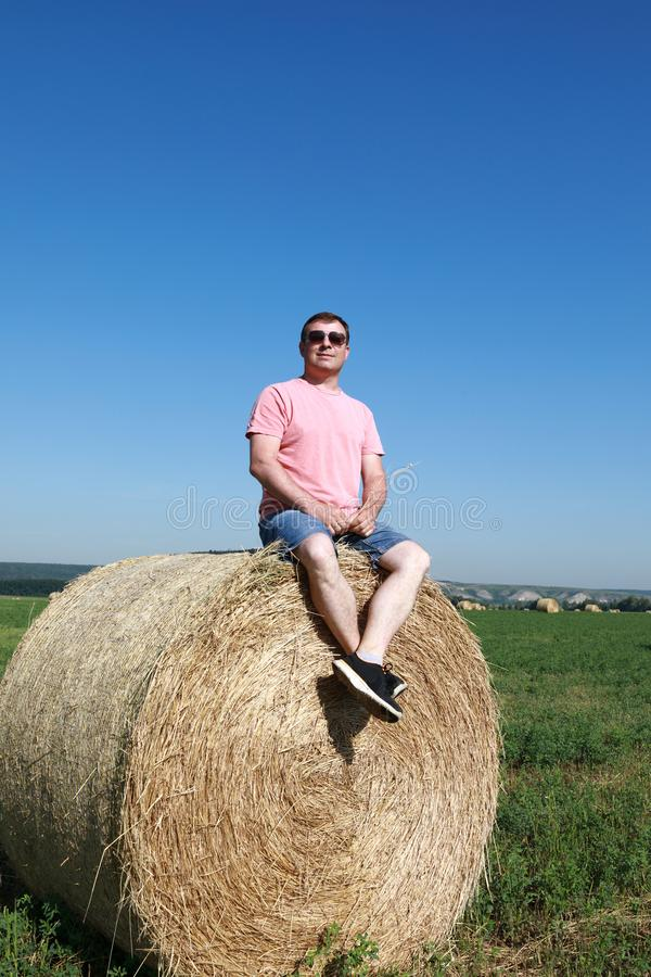 Person sitting on bale of straw. On field royalty free stock photography