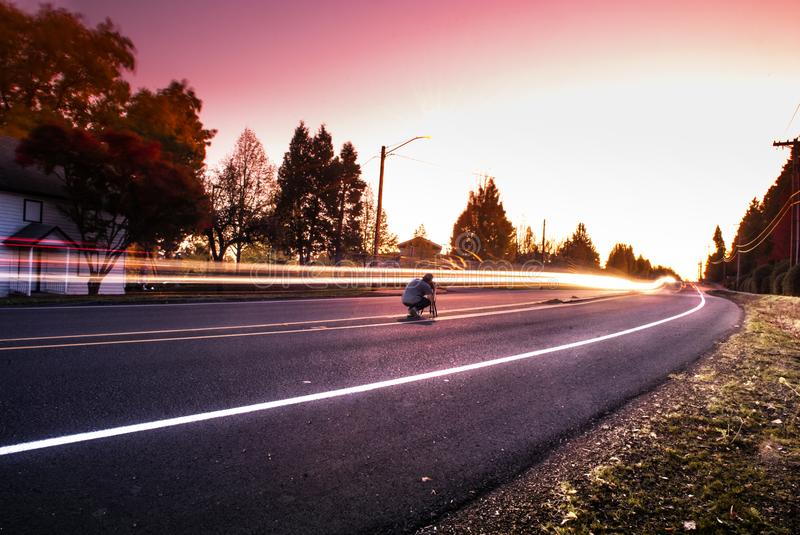 Person Sitting on Black Top Road during Twilight stock photography