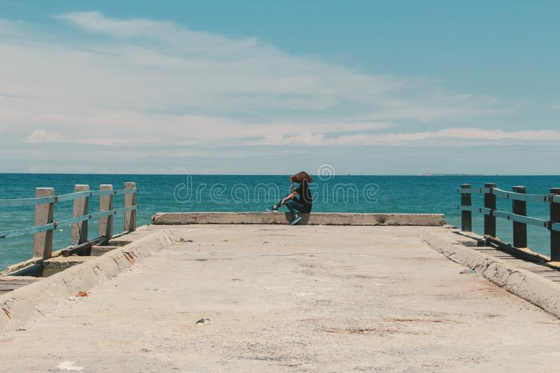 Person Sitting on the Edge of the Beach Dock royalty free stock photos
