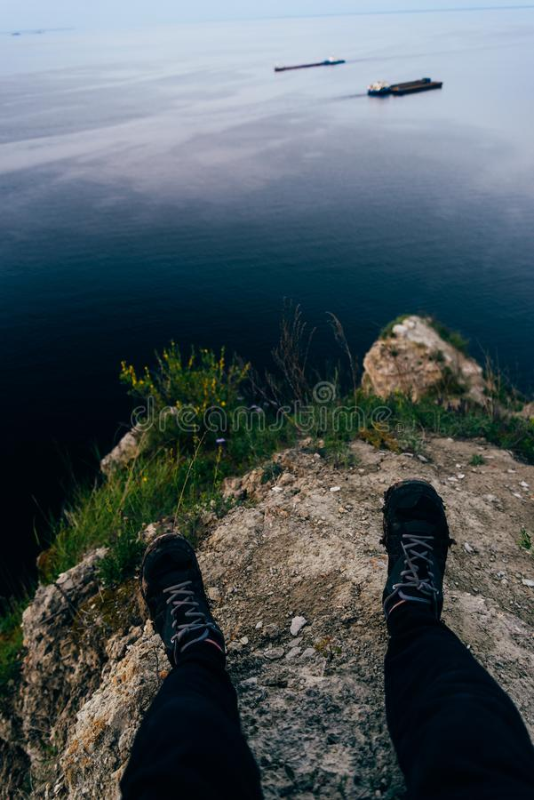 Person sitting on the edge. Of a cliff royalty free stock photo