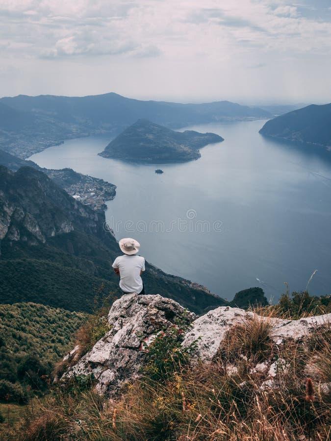 Person Sitting em um penhasco na montanha ao lado do LAK alpino italiano foto de stock