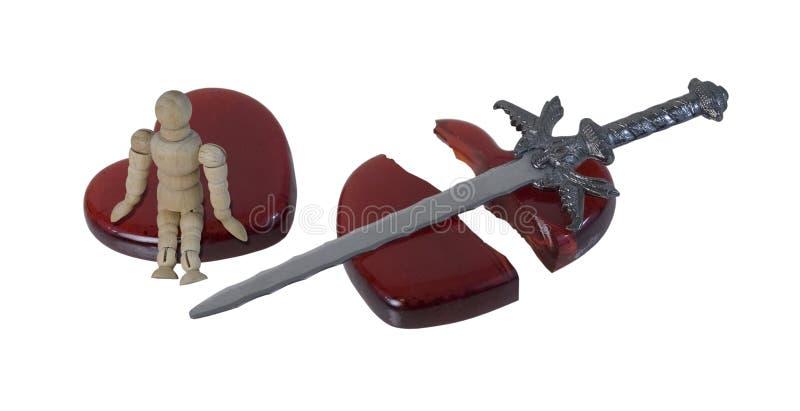 Person Sitting en un corazón roto con una espada imagen de archivo
