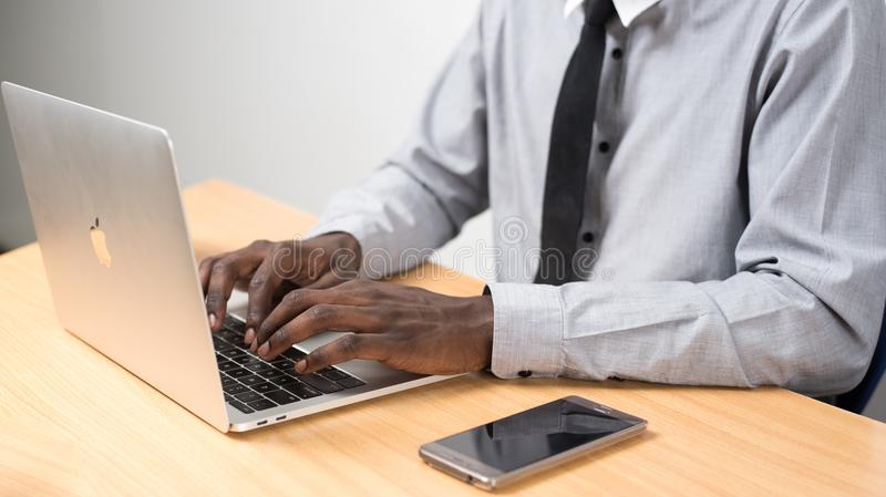 Person Sitting in Front of Table Using Laptop Beside Smartphone royalty free stock photography
