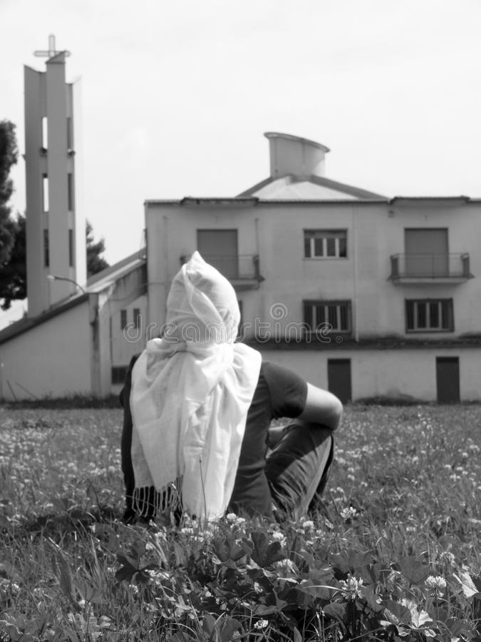 Person sitting in the grass wearing a white scarf on his head facing a building in the background. A person sitting in the grass wearing a white scarf on his stock image