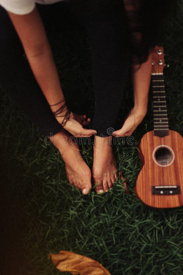Person Sitting on Green Grass Field Beside Ukulele royalty free stock photography