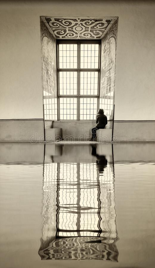 Person sitting by a large window reflecting in water. Creative image of person sitting by a large window reflecting in water stock photo
