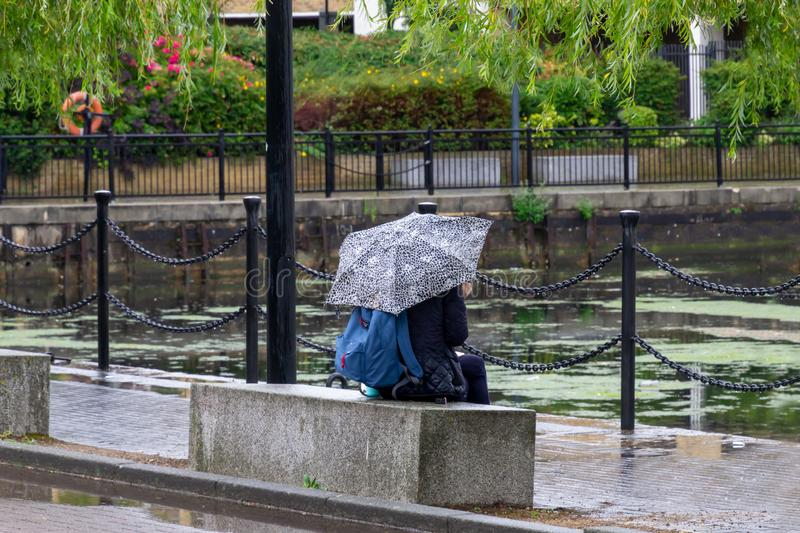 Person sitting lonely with umbrella. Concept of taking a break, solitude and thinking. Rain, water, lifestyle, sad, alone, loneliness, people, girl, scene stock photography