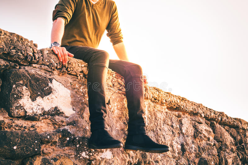 Person sitting. Low section of a person sitting on a rock in front of water stock images