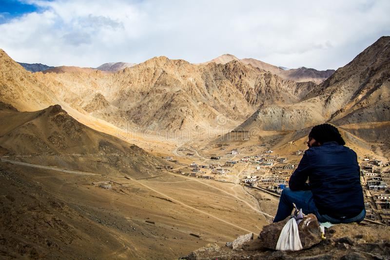 Person Sitting on Mountain Under White Sky royalty free stock photos