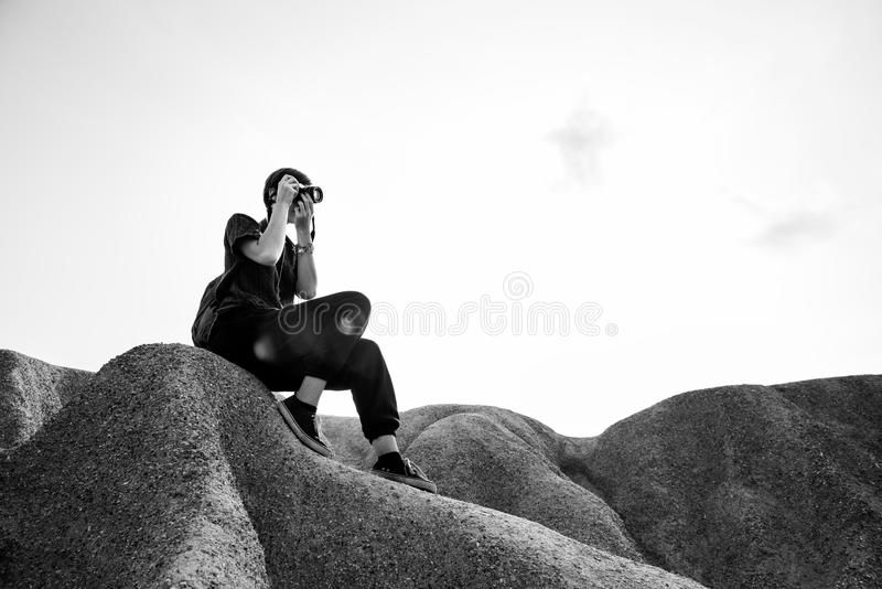 Person Sitting on Rocks Taking Photos stock image