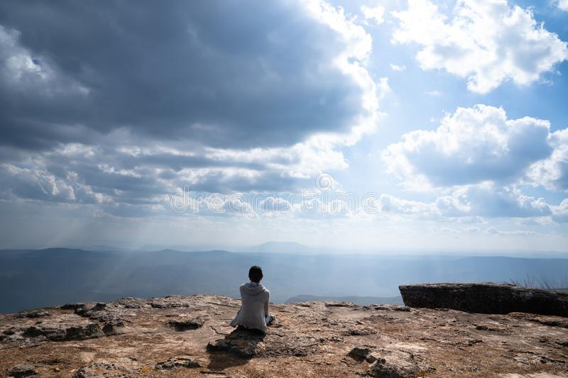 A person sitting on rocky mountain looking out at scenic natural view. And beautiful blue sky stock image