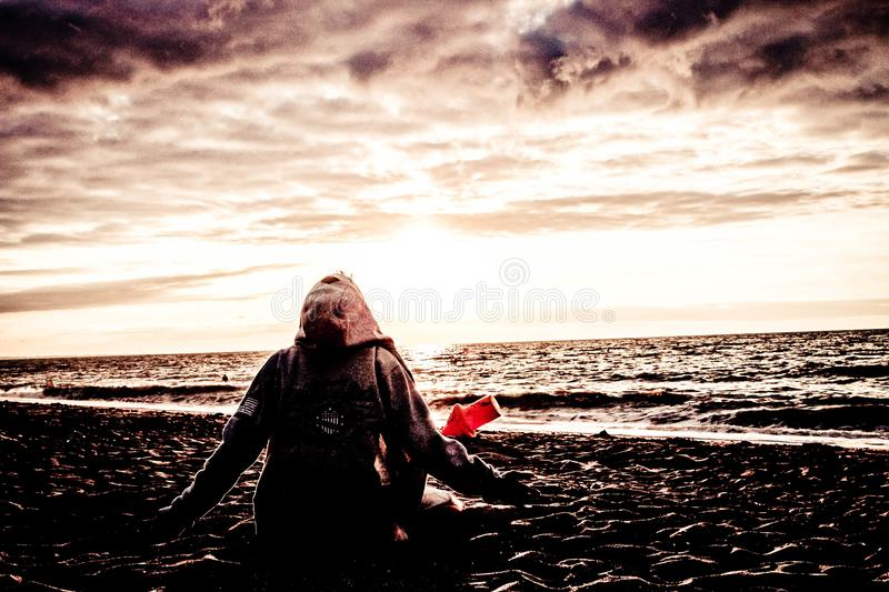 Person Sitting on Shore stock image