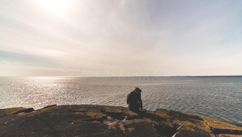 Person Sitting on Stone in Front of Sea Water stock photography