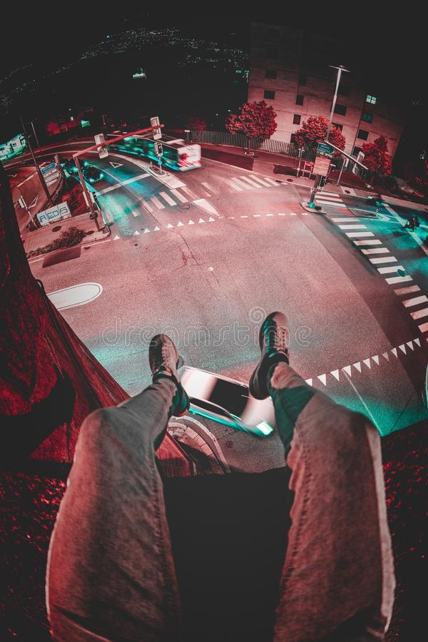 A person sitting on top of a building admiring the beautiful view of the city at night time. A vertical shot of a person sitting on top of a building admiring stock photos