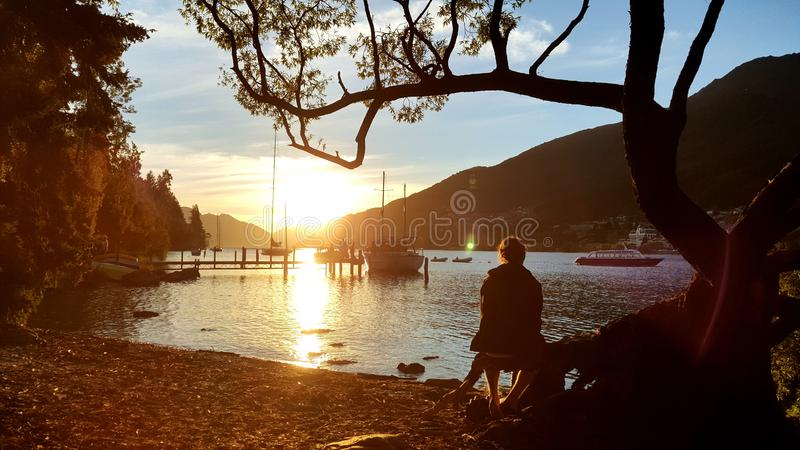 A person sitting under a tree looking into the distance. The picture feels peaceful, calm and quiet. This is perfect for travel or vacation wallpaper royalty free stock photo