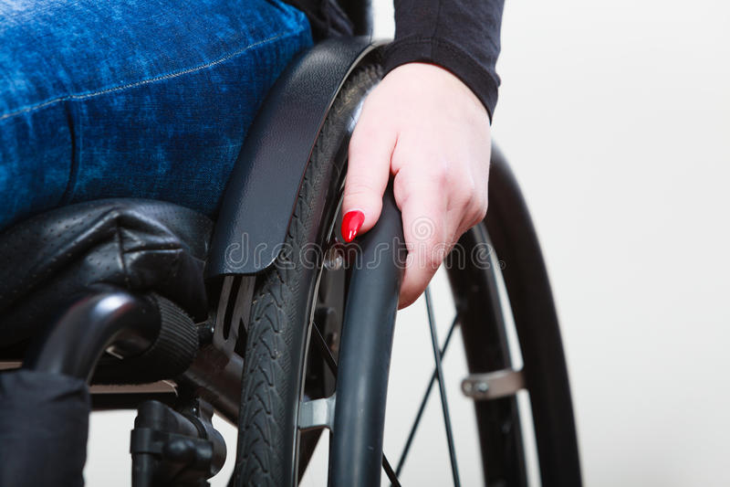 Person sitting on wheelchair. Female arm on wheel. Health disability rehabilitation concept royalty free stock photo