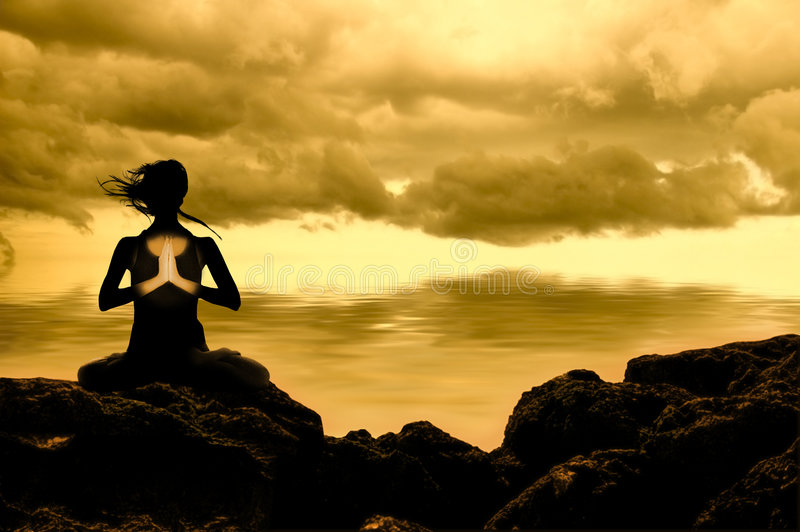 Person sitting yoga. A person sits in a yoga poise on a rocky surface at the edge of a body of water. A cloudy sky over golden waters serve as a backdrop