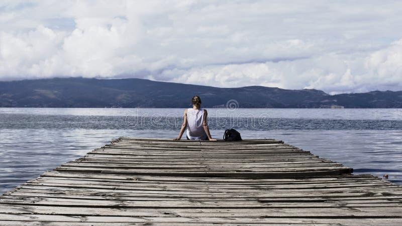 Person sitzt unter blauem Himmelswolken auf braunem Holzdock stockfoto