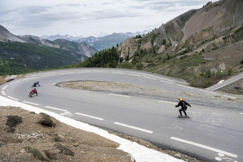 Person on skateboard leaves col d`izoard in the french alps of haute provence at great speed stock photo